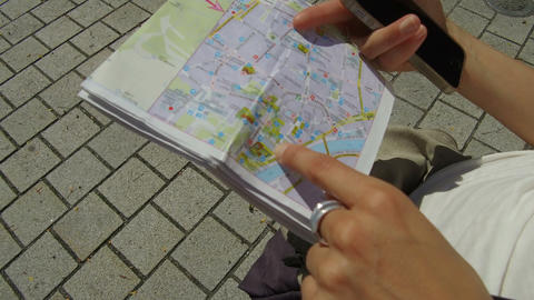 woman looks for information on a map Footage