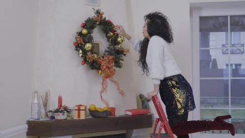 Young woman decorates a christmas wreath in the eve of holiday Footage