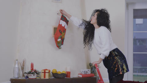 Pretty brunette decorates a wall over fireplace with sock and put gift inside it Footage