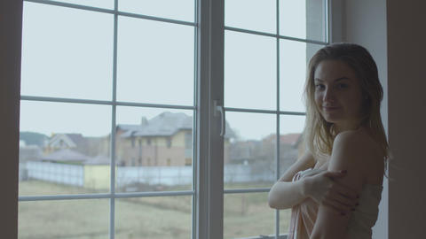 Seductive naked girl covered with blanket flirts with camera near the window Footage