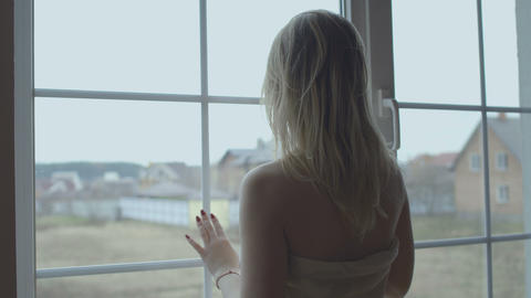 Beautiful woman wearing blanket on naked body looks at the window in the morning Footage