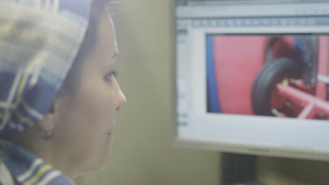 Employee Looks at Monitors Tire Rotation Slow Motion Footage