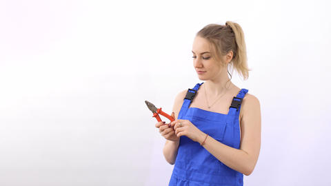 Young beautiful blonde wearing blue overalls with pliers at white background Footage