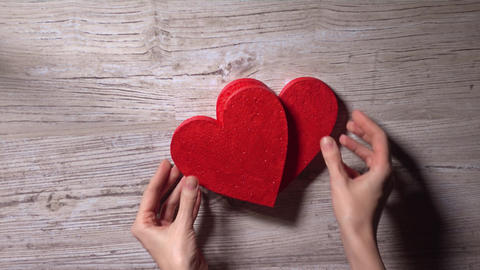 Female hands placing two red hearts on a wooden table, top view. Date, love Footage