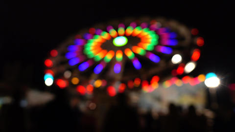 Theme park at night. Blurred spinning LED lit attraction. 4K background bokeh Footage