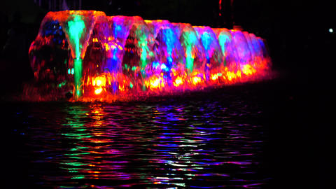 LED lit multicolor fountains at night and water ripple. 4K shot Footage