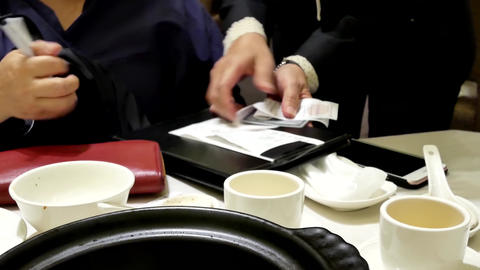 Motion of woman signing receipt after eating meal inside Chinese restaurant with Footage