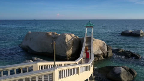 Girl in Red Watches Azure Ocean on Terrace Stairs Aerial Footage