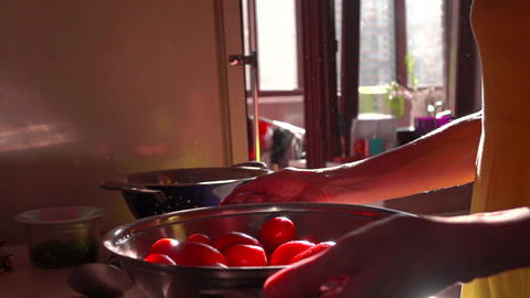 Girl tossing red tomatoes in a pan. Super slow motion video Footage