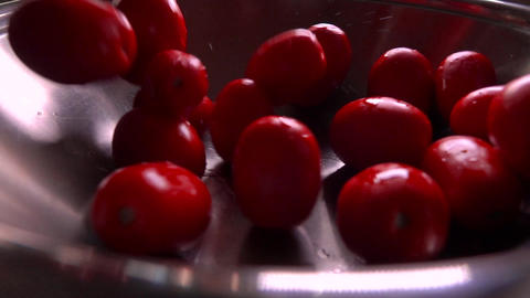 Super slow motion shot of wet tomatoes falling into a pan Footage