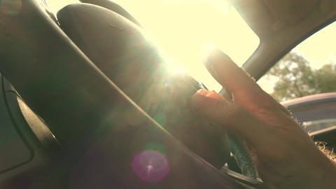 Happy driver drumming his fingers on the steering wheel against blazing sun Footage