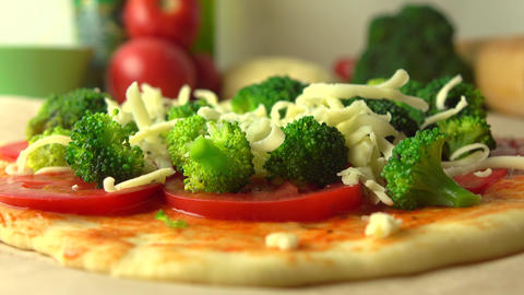 Pouring grated cheese over broccoli. Cooking homemade pizza, part of the set. 4K Footage