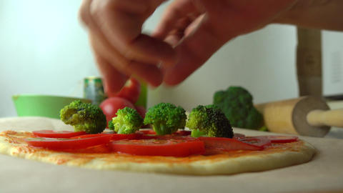 Man putting pieces of broccoli on homemade pizza. Cooking, part of the set. 4K Footage