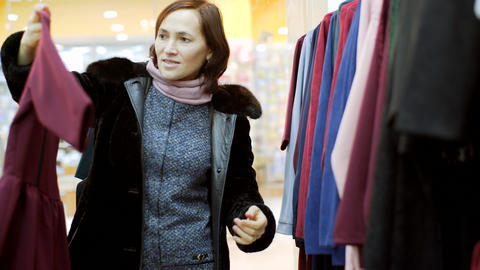 A woman in a fur coat chooses a dress in a clothing store Footage
