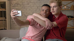 Two international gay friends, sitting on the couch, hugging, making selfies Footage