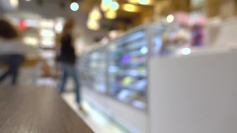 Young woman choosing chocolates in pastry shop. 4K background bokeh video Footage