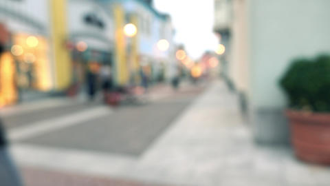 Blurred slim brunette girl with umbrella walking with her purchasings in paper Footage
