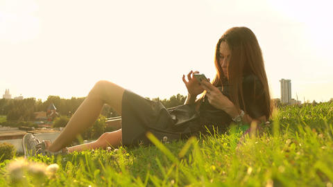 Beautiful brunette girl in black dress using her smartphone on the lawn. Leisure Footage