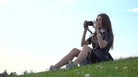 Beautiful brunette girl in black dress sitting on the lawn and making photos Footage