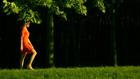 Beautiful brunette girl in red dress walking on the grass in the park from left Footage