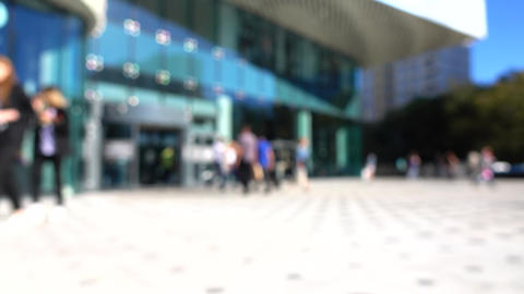 Blurred customers walking in modern shopping mall entrance. 4K background bokeh Footage