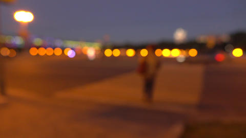 Blurred person crossing evening street. Lights and cars. 4K background bokeh Footage