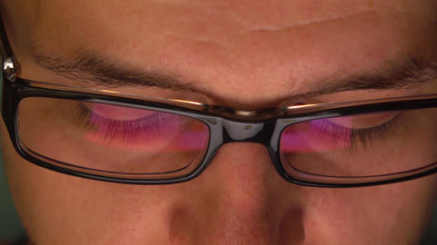 Man's dark rim glasses reflecting tablet computer in the dark. 4K extreme close Footage