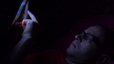 Man in black rim glasses using his touchscreen device in dark room. Screen Footage