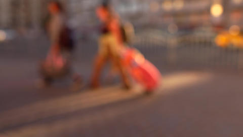 Blurred tourists walking on the street with their luggage. 4K background bokeh Footage