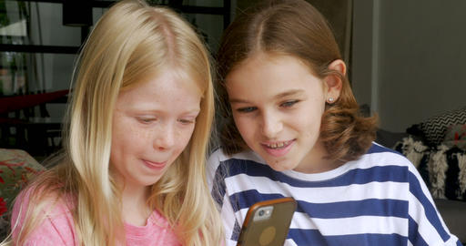 Authentic moment of two young girl friends laughing and smiling while using a Footage