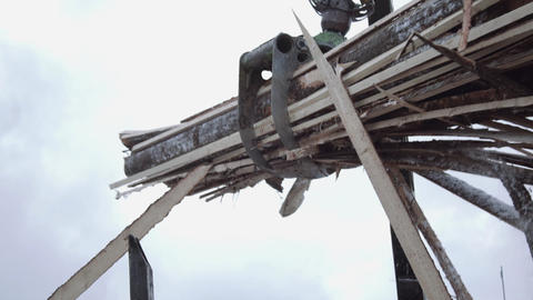Truck loader crane claw lifts up lumber wooden waste Live Action