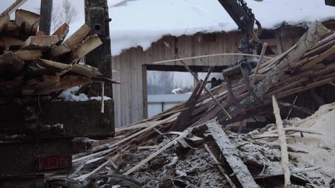 Truck loader crane claw picks up lumber wooden waste Live Action