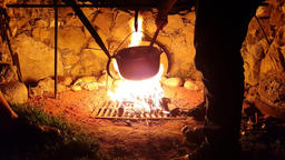Cooking food at the stake. Tourists interfere with soup in a large saucepan on Footage