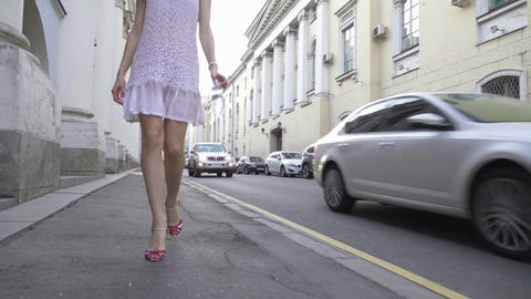 Beautiful brunette girl in white dress walking at camera on Moscow center street Footage