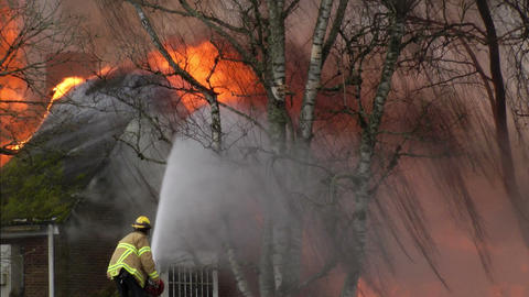 Fireman sprays water on a building consumed by fire Stock Video Footage