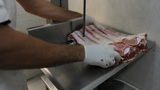 Butcher Shop Butcher Man Hand Cutting Raw Meat With Meat Chopper stock footage