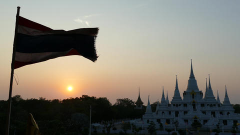 Sunset at the Buddhist stupa with multiple spires with the Thai flag Footage