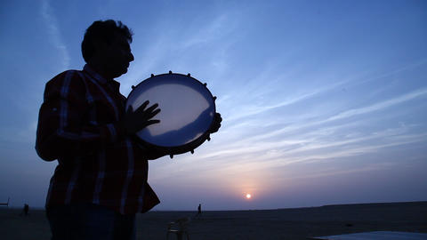 Silhouette of man plays the drum in sun set Footage