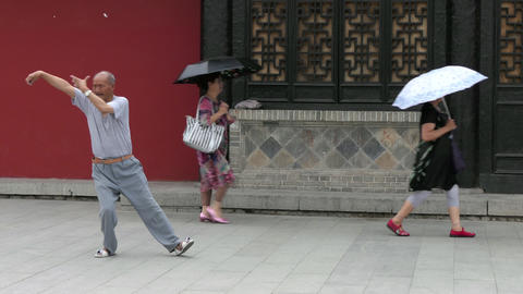 Elderly Chinese Man Practicing Tai Chi In Old City Square Footage