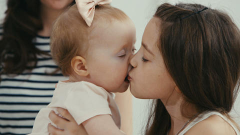 older sister kissing her baby sister Footage