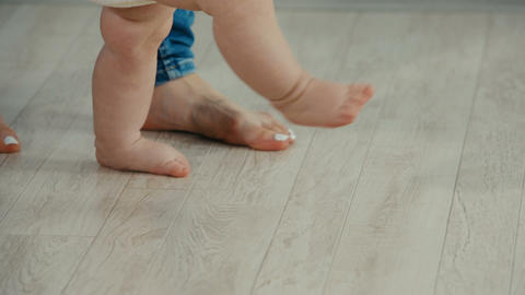 Legs of mother and baby. Baby Daughter Take First Steps Footage