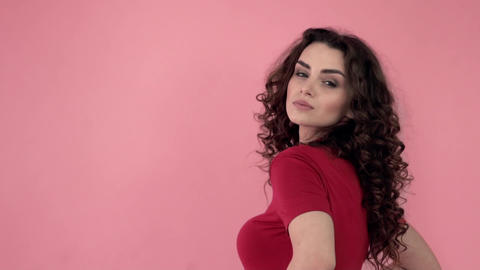 Beautiful fashionable girl with long curly hair in a red T-shirt. Girl in the Footage