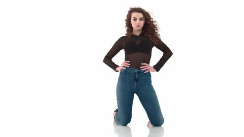 Curly-haired girl in black body and jeans kneeling on a white background slow Footage