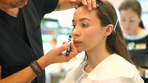 Professional eye makeup. Makeup artist and beautiful brunette girl Live Action
