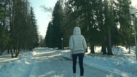 Young sporty woman walks in snowy park on sunny day Live Action