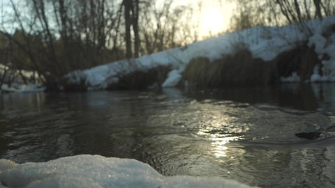 Spring stream at sunset with reflection of the sun Footage