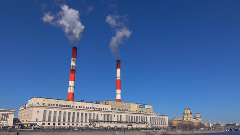 Obsolete heat electric plant and smoke from stacks against blue sky. 4K video Footage