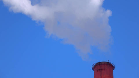 Top of smoking red smoke stack against sunny blue sky. 4K telephoto lens video Footage