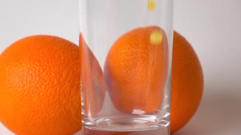 Two whole oranges and orange juice being poured into glass. Super slow motion Footage