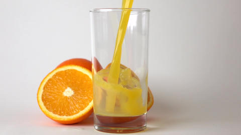 Cut and whole orange and orange juice being poured into glass. Super slow motion Footage